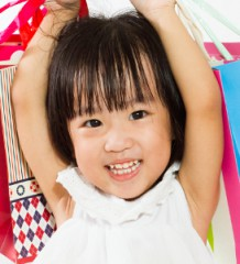 Asian Chinese little girl with shopping bag in white isolated background.
