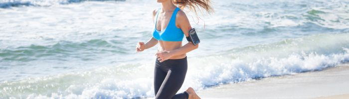 Young woman jogging on the beach wearing leggings