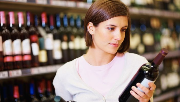 Young woman selecting wine bottles at supermarket