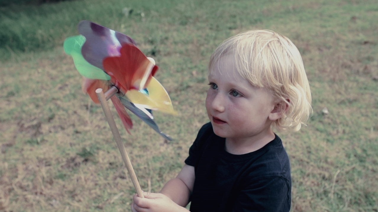image of a child with a toy windmill